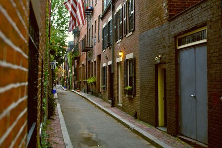 rowhouses: classic boston street with gas lamp, shuttered windows and flower boxes. brick sidewalk and american flag