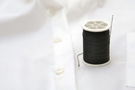spool of black thread on white shirt with needle Imagens