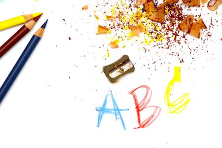 bright colorful image of freshly sharpened colored pencils, red, blue and yellow, with shavings on white drawing paper with numbers, letters and pencil sharpener photo