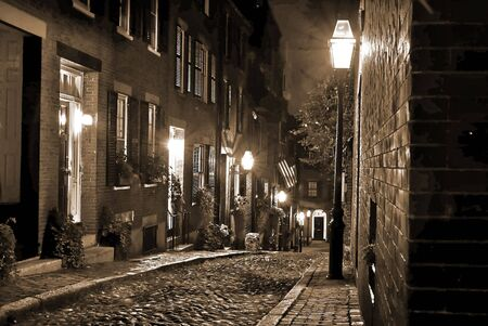 19th century: old 19th Century cobble stone road in Boston Massachusetts, lit only by the gas lamps revealing the shuttered windows and brightly lit doorways of the rowhouses on Acorn Street