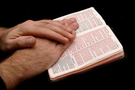 hands of man resting on bible, reading the book of saint matthew, on black background Banco de Imagens