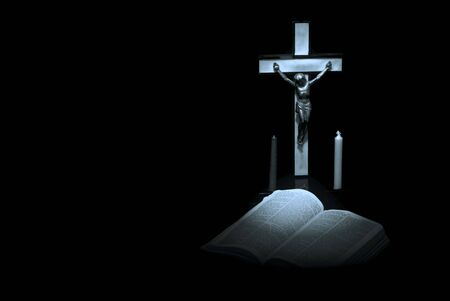 somber: somber blue toned image of bible, cross, and prayer candles against a black background with blank space Stock Photo