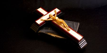 image of an old crucifix laying on top of an ancient leatherbound bible photo