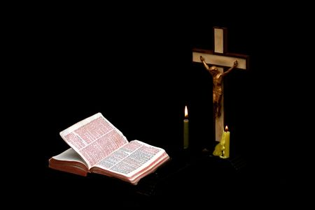 mage of a prayer crucifix with two candles set out before a bible open to the book of St. Matthew, the bible is well llit with softer lighting on the cross photo