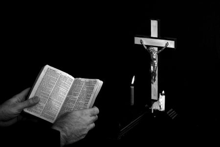 man reading bible near prayer crucifix with candles burning, book is open to st. matthew photo