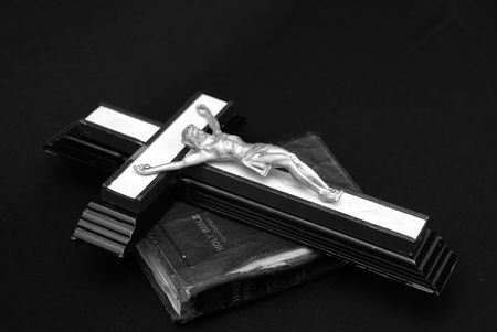 striking black and white image of an old crucifix laying on top of an ancient leatherbound bible photo