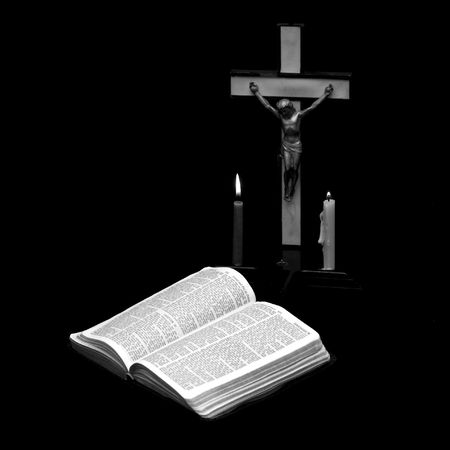 stark black and white image of a prayer crucifix with two candles set out before a bible open to the book of Jeremiah photo