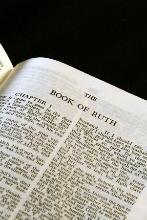 bible series, detail of an old antique holy bible against a black background open to the book of ruth
