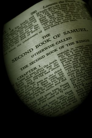bible series, detail of an old antique holy bible against a black background open to the second book of samuel otherwise called the second book of the kings finished in sepia