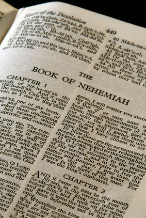 bible series, detail of an old antique holy bible against a black background open to the book of nehemiah old testament