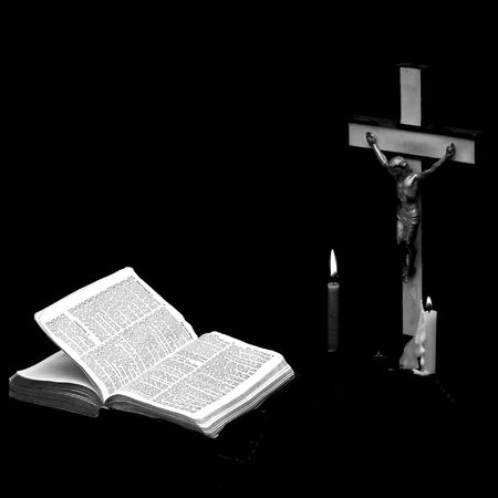 stark black and white image of a prayer crucifix with two candles set out before a bible open to the book of matthew, square format Stock Photo - 2406865
