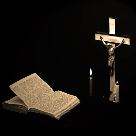 sepia image of a prayer crucifix with two candles set out before a bible open to the book of matthew, square format photo