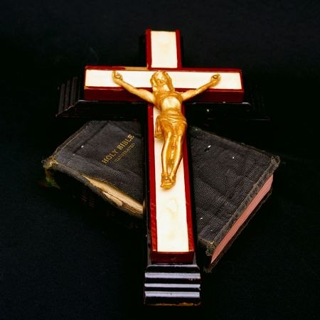 folded hands: full color image of an old crucifix laying on top of an ancient leatherbound bible