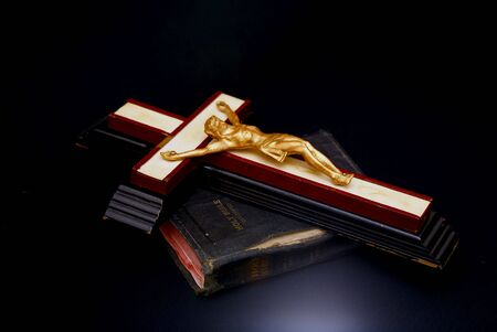 dynamic glowing  image of an old crucifix laying on top of an ancient leatherbound bible photo