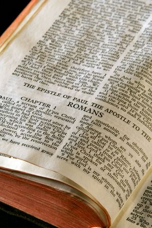 Bible Series. close up detail of antique holy bible open to the gospel according to the epistle of paul the apostle to the romans in the new testament