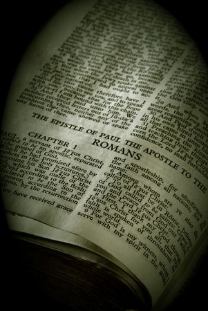 Bible Series. close up detail of antique holy bible open to the gospel according to the epistle of paul the apostle to the romans in the new testament finished in sepia