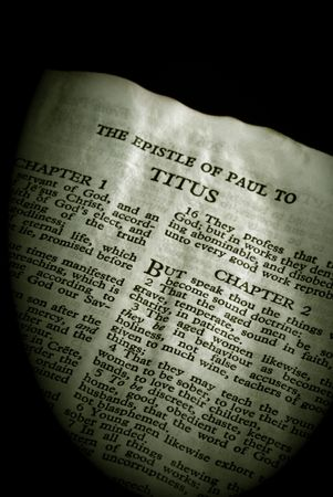 apostle paul: Bible Series. close up detail of antique holy bible open to the gospel according to the epistle of paul the apostle to titus in the new testament finished in sepia