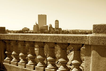 parapet: sepia toned image of boston skyline in the distance beyond, cement balustrade, parapet  of roof top in boaton massachusetts