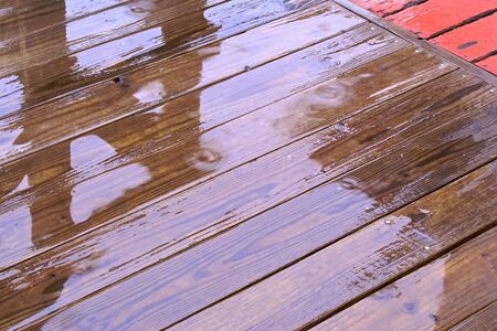wet planks of a wooden deck as it is raining, creating a shine on the surface
