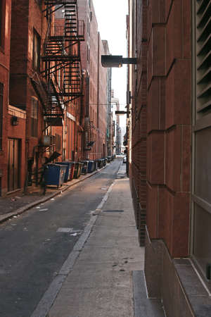 Public alley in boston showing brick buildings, dumpsters and fire escape               Stok Fotoğraf