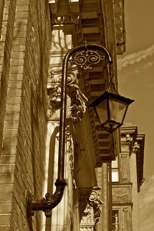 detail of old ornate gas lamp attached to outside of building