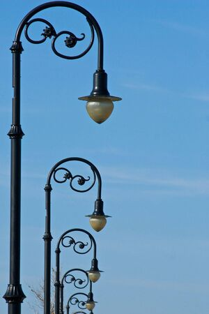 receding: row of old fashioned street lights receding into the distance Stock Photo