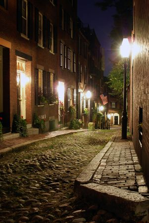 Sepia toned image of an old 19th Century cobble stone road in Boston Massachusetts, lit only by the gas lamps revealing the shuttered windows and brightly lit doorways of the rowhouses on Acorn Street