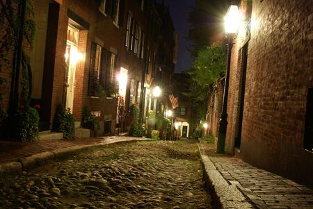 colonial: old 19th Century cobble stone road in Boston Massachusetts, lit only by the gas lamps revealing the shuttered windows and brightly lit doorways of the rowhouses on Acorn Street