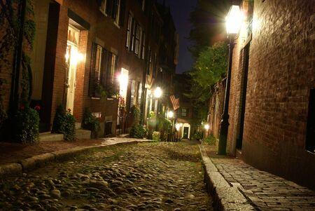 cobble: vecchio 19 � secolo Cobble pietra strada a Boston Massachusetts, illuminato solo da lampade a gas che rivelano l'shuttered finestre e porte illuminate del rowhouses a Acorn Street