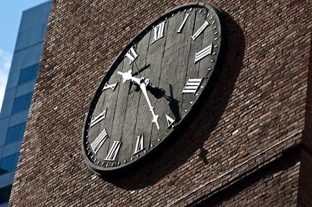 black clock face on brick with roman numerals
