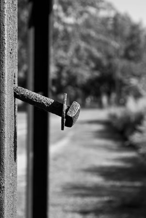 metal post: rusted bolt sticking out of rusted metal post in black and white Stock Photo