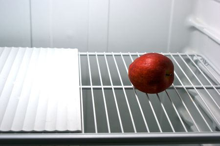 one red delicious apple alone in an empty refrigerator photo