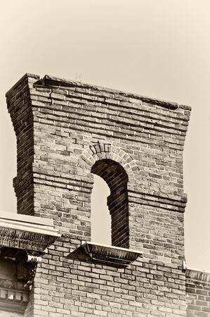 old brick arch high in the sky finished in sepia Banco de Imagens