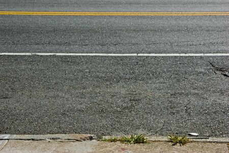 yellow line: asphalt covered street showing white line and double yellow line and portion of sidewalk