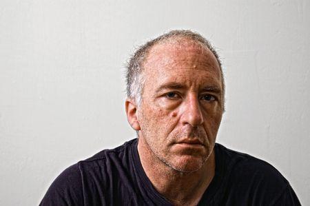 woe: gruff looking man looking tired gazing at viewer