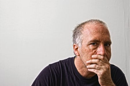 beautifully detailed real portrait of haggared looking adult white man staring intensely at the viewer with hand over mouth and black t-shirt Stock Photo