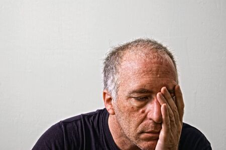 woe: beautifully detailed real portrait of tired and weathered looking adult white man holding his head with his hand Stock Photo