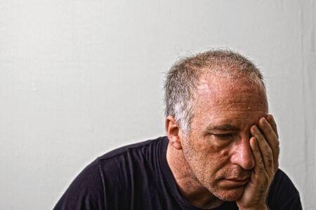 wanhopig: prachtig gedetailleerde echte portret van haggared zoekt volwassen blanke man die zijn hoofd als een hoofdpijn of in diepe wanhoop Stockfoto