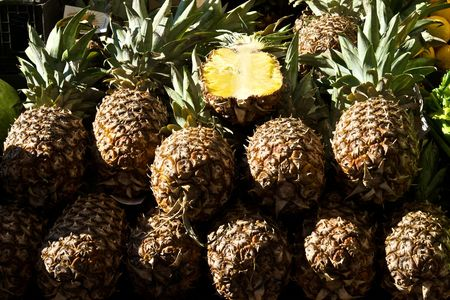 stack of fresh ripe pineapples at outdoor market, with one cut open