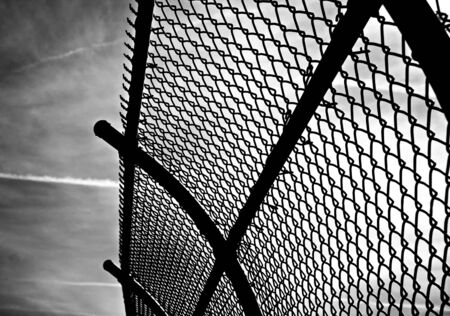 chain link: curved chain link fence against dramatic sky