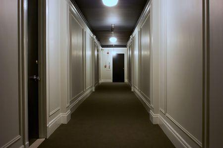 long interior hallway showing doors, lights, ceiling, carpet Stock Photo