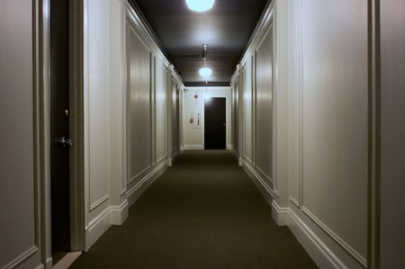 hallway: long interior hallway showing doors, lights, ceiling, carpet Stock Photo