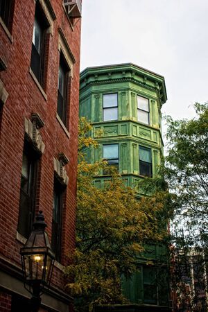oxidized: old oxidized building rises up over trees in the fall on beacon hill in boston massachusetts Stock Photo