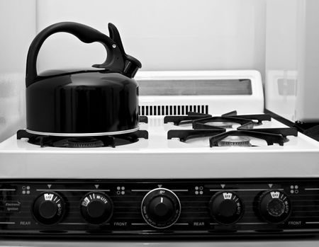gas stove: teapot sits on vintage stove in this black and white image of a kitchen