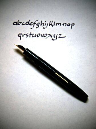펜으로 양피지 종이에 서예로 쓰여진 알파벳 스톡 콘텐츠