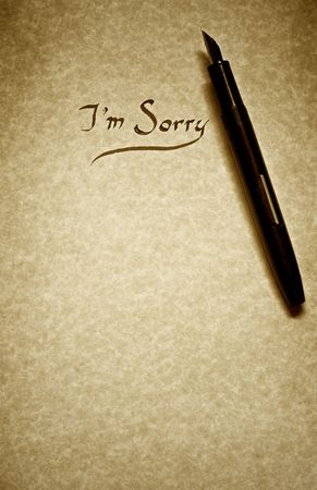i am sorry: i am sorry leter being written in calligraphy on parchment paper with pen finished in sepia tone