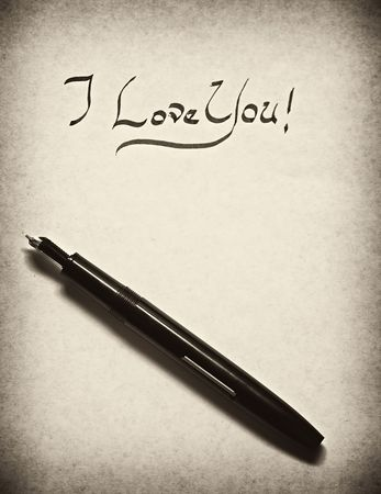 i love you leter being written in calligraphy on parchment paper with pen with old fashioned monotone finish photo