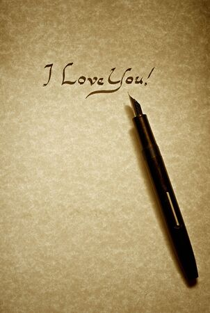 manuscrita: i love you leter being written in calligraphy on parchment paper with pen finished in sepia Banco de Imagens