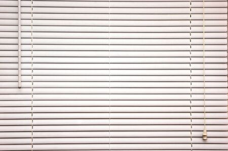 background image of off white mini blinds inside home closed