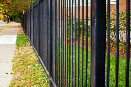lack iron fence runs along this tree lined sidewalk in boston massachusetts